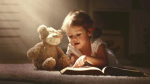 Child reading a book with a teddy bear
