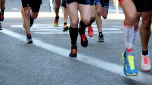 Legs and shoes of runners on road