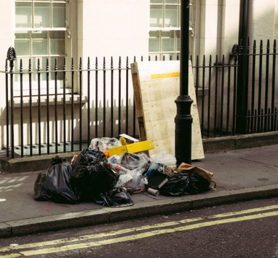 Bin bags and loose rubbish on pavement outside of a building